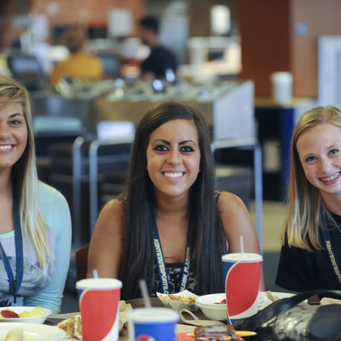 Three new friends pose for a photo during lunch time at Destination Kent State. The summer program is attended by all incoming freshmen and their parents.