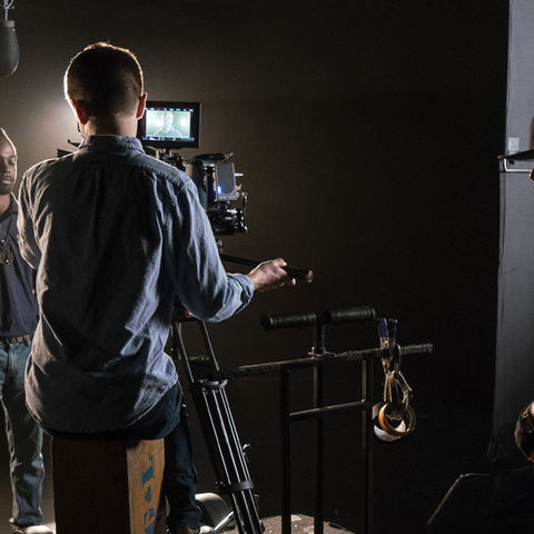 Kent State graduates, students and crew adjust lights for the principle shot of the new Kent State commercial.
