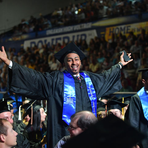 Finish Line Feeling.  A Kent State student embraces the moment after receiving his degree during the Oct. 18 undergraduate commencement ceremony at the Memorial Athletic and Convocation (MAC) Center.