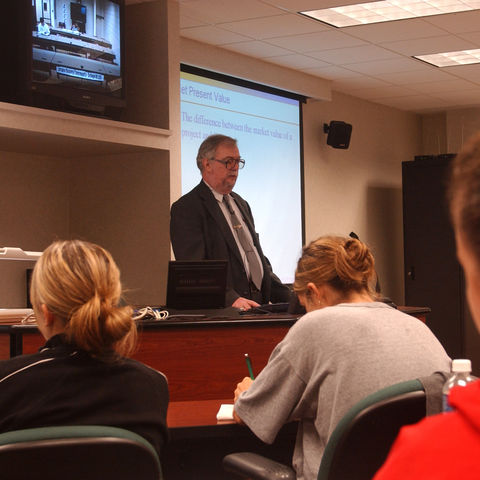Dr. James Boyd, professor of finance, benefits from the advanced technology in the Vaughn Hoover Executive Classroom while teaching a finance class in the College of Business.