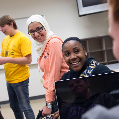 Kent State University students discuss research material before the start of a class session.