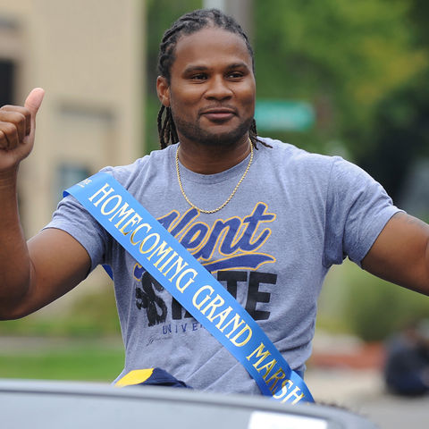 Kent State alumnus Josh Cribbs waves to Kent State students and local residents attending the 2016 Kent State Homecoming Parade. Cribbs returned to campus to serve as the Homecoming Parade Grand Marshal.