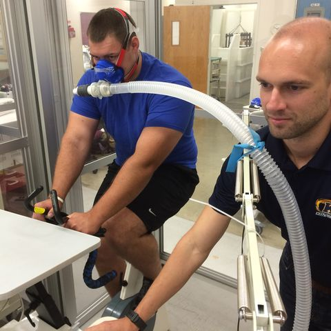 Alexander Ceh, 23, an undergraduate exercise science major from Grafton, demonstrates riding an indoor bike with a mask in a controlled low oxygen environment, while Jeremiah Vaughan analyzes his levels.