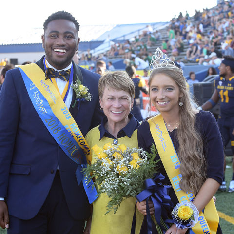 Kent State President Beverly J. Warren poses with 2018 Homecoming King Jordan Euell and Queen Jennifer Uren on the field at Dix Stadium.