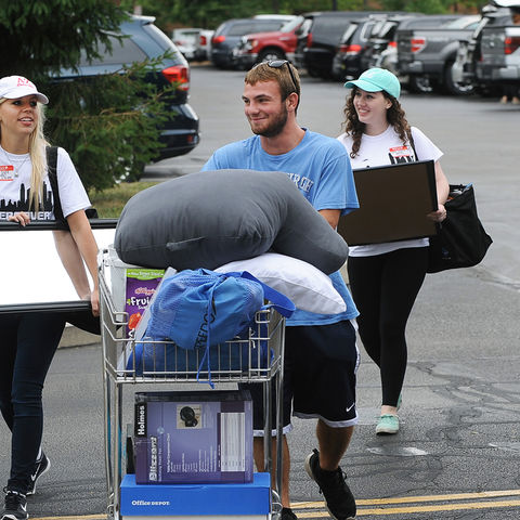 An incoming freshman and his family is assisted by volunteers during move-in day near Manchester Hall.