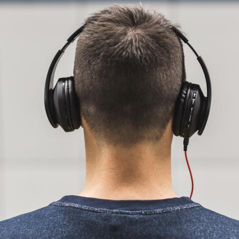 Man turned around wearing over the ear headphones.