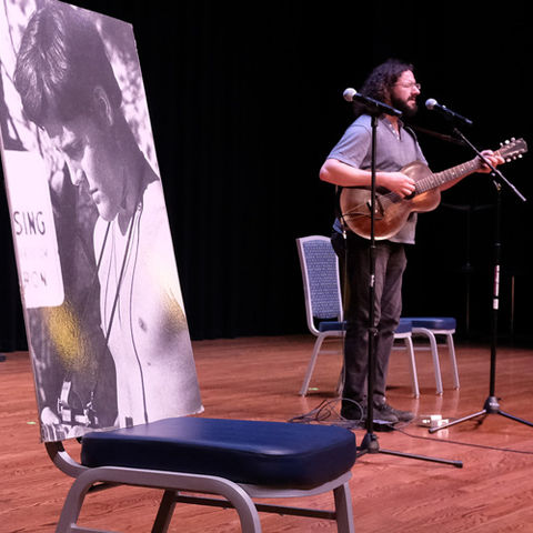 A singer performs on stage in the Kent Student Center Ballroom during the 49th annual May 4 Commemoration.