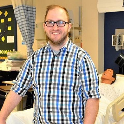 Nursing student Andrew Loos standing in the nursing skills lab