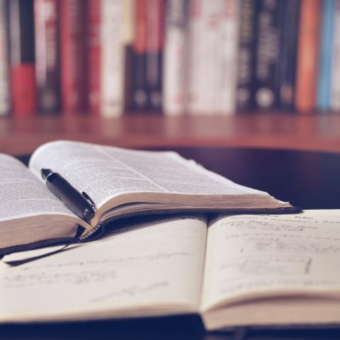 Image of a book and notebook laid out on a table in front of a bookcase.