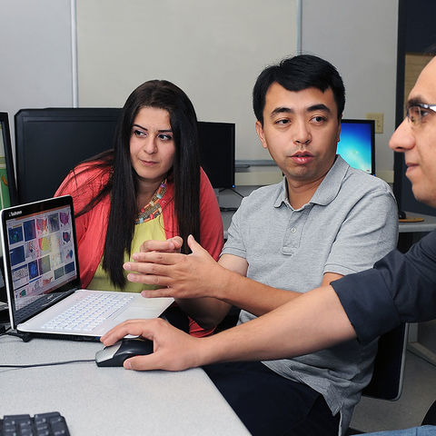 Ye Zhao, associate professor of computer science in the College of Arts and Sciences, works with students in the Mathematics and Computer Science Building.