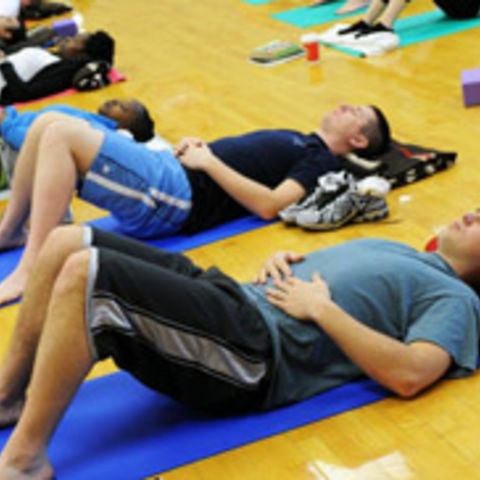 Nursing students practice a self-care exercise on yoga mats.