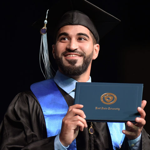 A Kent State University graduate displays his diploma for family and friends during the baccalaureate degree ceremony in the Memorial Athletic and Convocation Center (MAC Center).