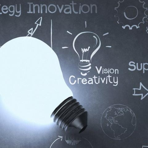 Image of a chalkboard with a lightbulb laying on top
