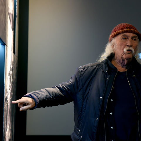 Singer David Crosby points at a photo of the May 4, 1970, shootings that killed four Kent State students.