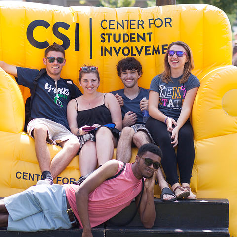 A group of Kent State students pile onto the Center for Student Involvement's oversized inflatable couch.