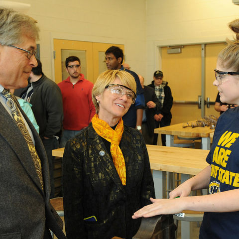 Dennis Eckart, chair of the Kent State Board of Trustees, and Kent State President Beverly Warren speak to a student working in one of the shops in the new Aeronautics and Technology Building.