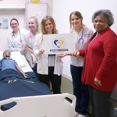 ollege of Nursing students, as well as Senior Lecturer Elaine Thomas and Dean Barbara Broome thank our Giving Tuesday supporters in the simulation lab, next to a mannequin in a hospital bed