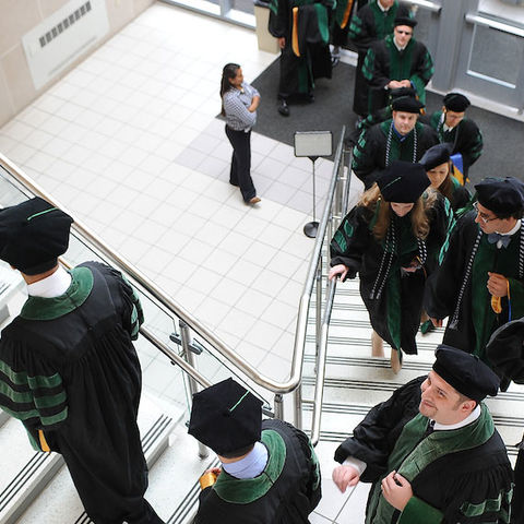 Faculty and staff walk up the stairs on the way to Commencement.