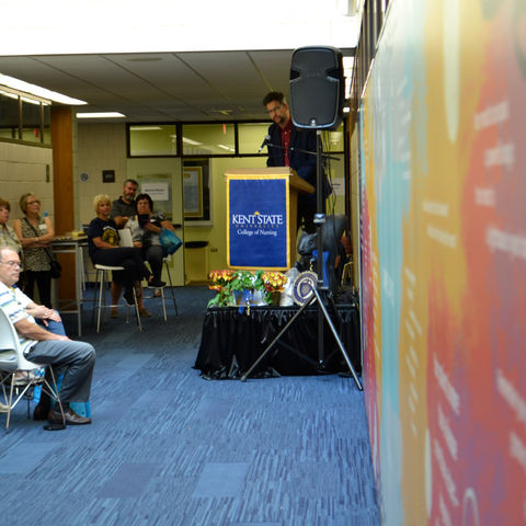 David Hassler, director of the Kent State University Wick Poetry Center, unveils 'Some Days' during the 'Nursing 50 Years Strong' reception