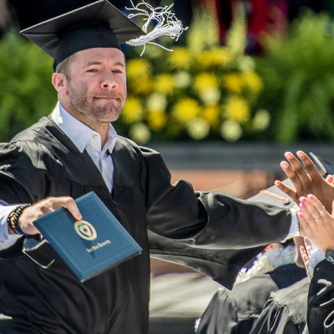 New England Patriots wide receiver Julian Edelman is congratulated by fellow Kent State graduates at the One University Commencement held at Dix Stadium.