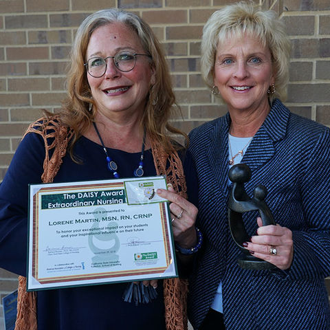 Senior Lecturer Lorene Martin (left) holds her DAISY Award certificate next to Assoc. Dean Tracey Motter (right)