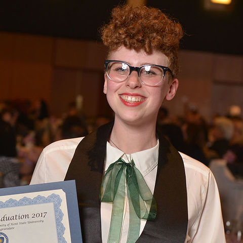 A Kent State University student proudly displays an award certificate during the university's Lavender Graduation ceremony, which honors the achievements of graduating lesbian, gay, bisexual, transgender, queer and ally students.