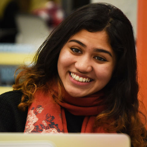 Student smiling and chatting in the Kent State library