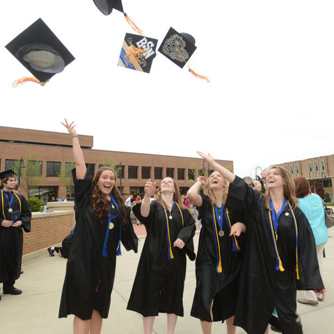 BSN graduates throw their caps in the air after their commencement ceremony, 2014