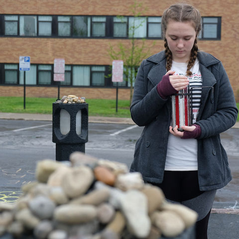 A student stands holding a candle in front of a May 4 marker in the Taylor Hall parking lot.
