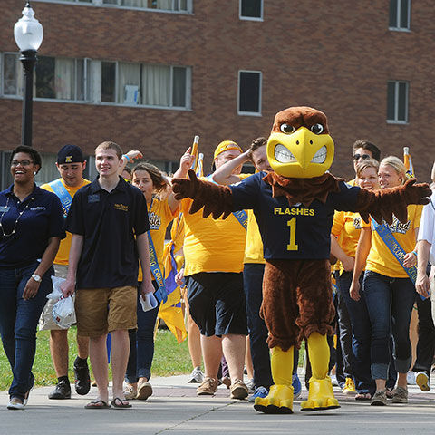 Flash mascot walking in parade with crowd