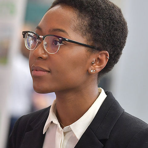 African American woman with glasses in professional dress at job fair