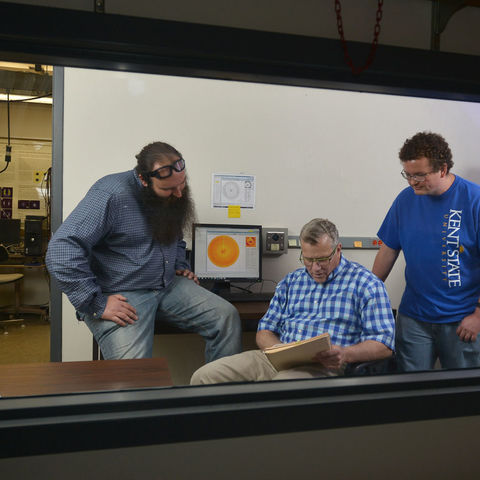 Michael Fisch (center), assistant professor in Kent State's College of Applied Engineering, Sustainability and Technology, works with students in an X-ray lab in the Science Research Building.