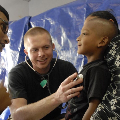 A parent holds their adolescent child while doctors examine him.