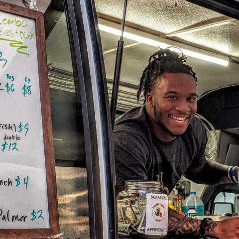 Photo of student inside of a food truck, smiling for the camera