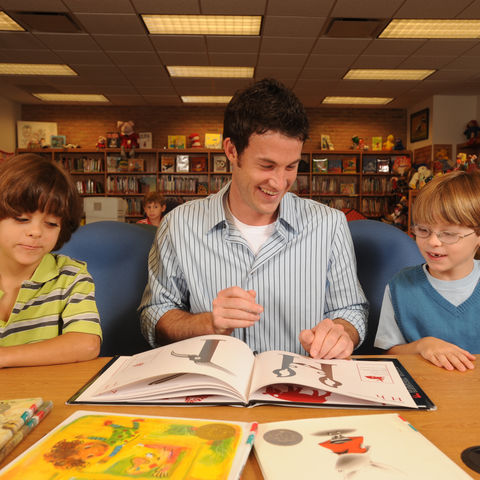 A library and information science student reads to children in SLIS's Reinberger facility.