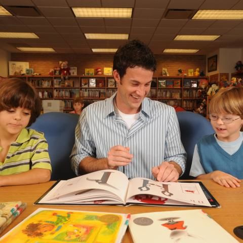 A Library and Information Science student reads to children in the SLIS Reinberger facility.