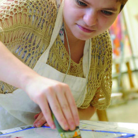 An art student works on a silk screen project
