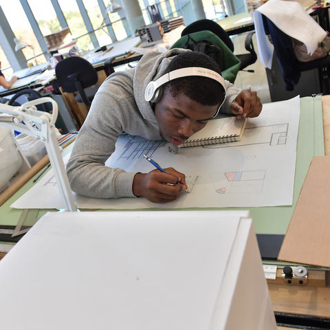 Student drawing with headphones