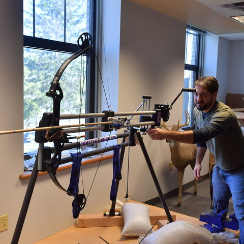 Assistant Professor of Anthropology, Dr. Metin Eren, eyes up a target as he prepares to fire an arrow affixed with a hand-crafted replica of a Clovis arrowhead.