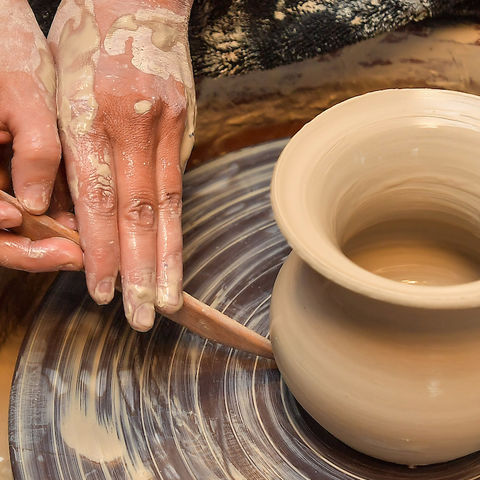 A woman's hands work a clay pot on a turntable