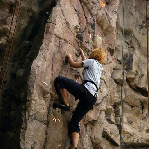 Student climbing a rock wall