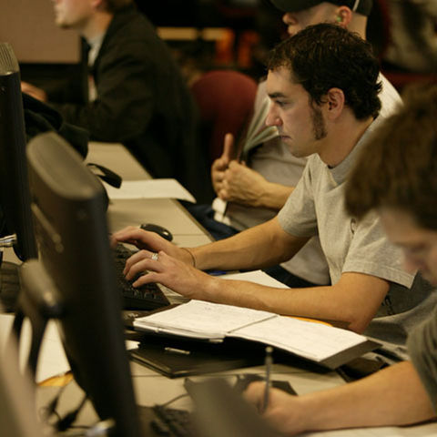 Students sit at a row of computer stations, reviewing their financial information