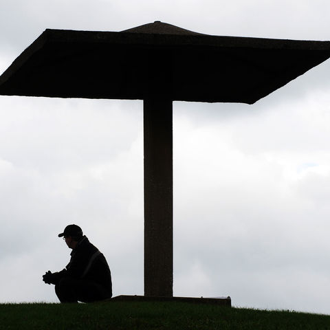 A visitor to the Kent State campus rests on the Pagoda during the 2011 Commemoration of the May 4, 1970 shootings that left 4 students dead.