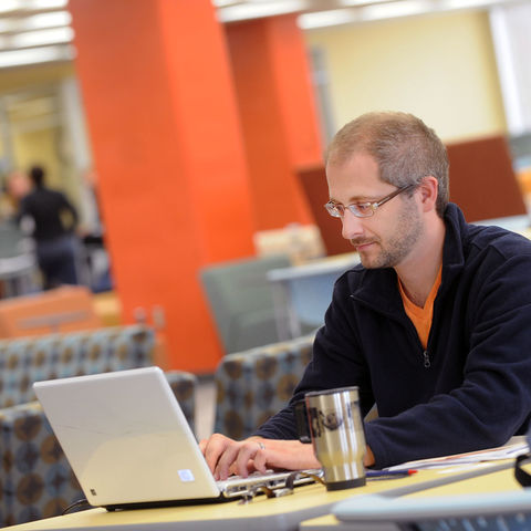 A student uses his downtime to study and relax in the Fab Fourth on the fourth floor of the library.