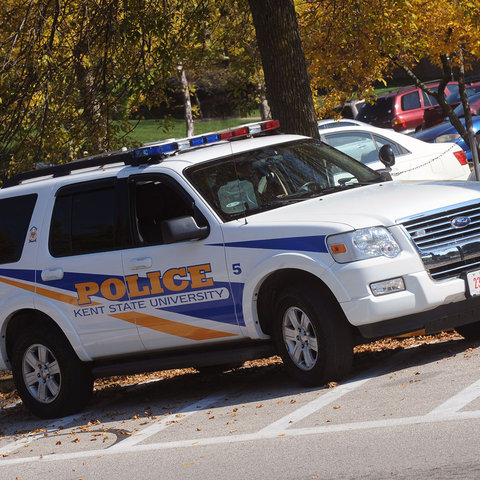 A Kent State University Police SUV sits parked in front of a packed parking lot.