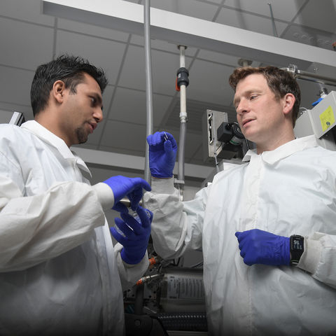 Dr. Björn Lussem, assistant professor of physics, right, works with a student in his lab
