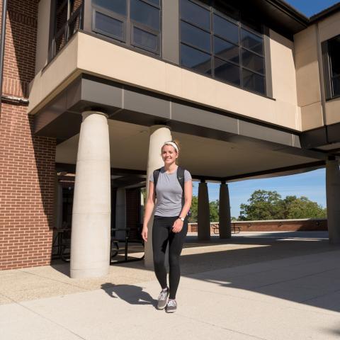female student walking underneath bridge lounge of Stopher-Johnson residence halls.