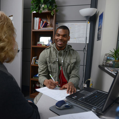 A student in the College of Communication and Information works with his advisor to chart his educational path.