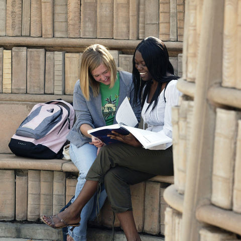 Two students sitting by the books in the Brain Plaza.
