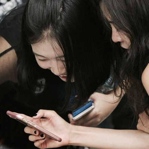 Two students looking at their phone